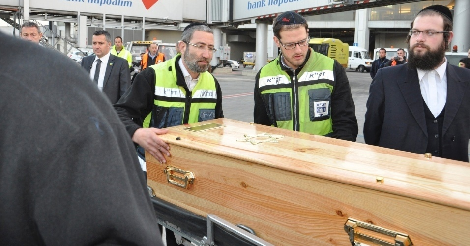 Voluntários carregam um dos caixões com vítimas de massacre em escolar francesa do avião para uma van no Aeroporto de Ben Gurion, em Tel Aviv, em Israel. A aeronave que transportava os corpos das quatro vítimas chegou na manhã desta quarta-feira (21) na cidade.