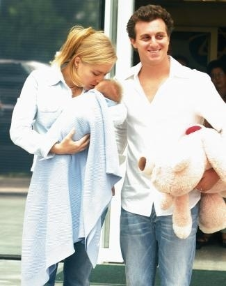O casal deixa a maternidade com o primeiro filho. Aliviada, Angélica finalmente pôde levar Joaquim para casa, oito dias após o nascimento do bebê (mar.2005).