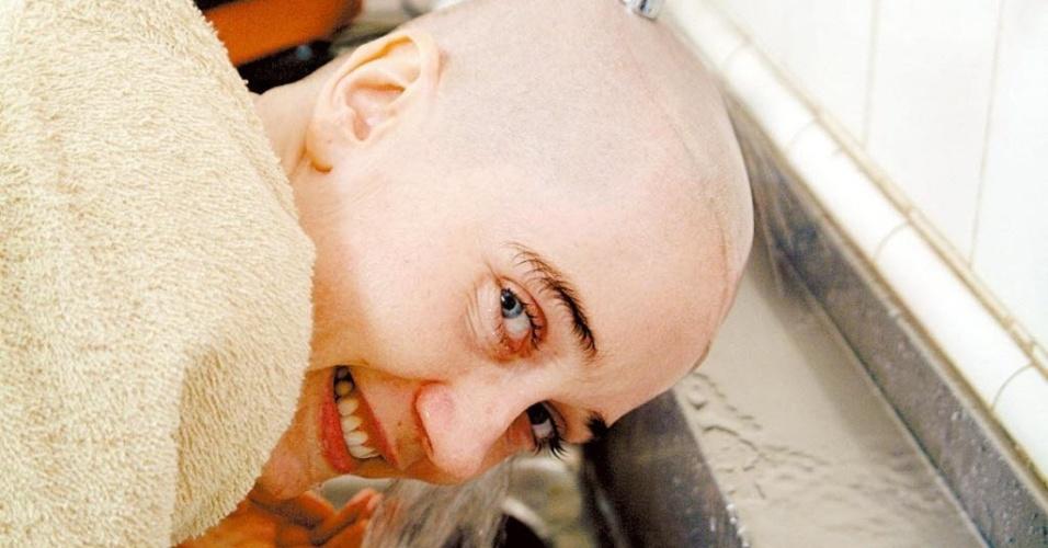 """A atriz Camila Morgado molha a cabeça após raspar os cabelos para filmar cenas como Olga Benário em um campo de concentração nazista, para o longa """"Olga"""" (2004)"""
