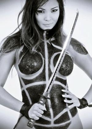 """Carol Nakamura, assistente de palco do programa """"Domingão do Faustão"""", estrela mais um ensaio sensual. Após estampar a capa da """"Sexy"""" de novembro do ano passado, a bela foi clicada nua com o corpo pintado para a """"Mensch"""". Durante o ensaio, Carol encarnou uma ninja sexy com uma espada de samurai"""