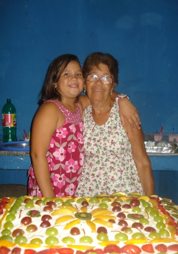 Em frente a um bolo cheinho de frutas, posam Milena com a bisavó Isabel. Elas são de Itaguaí (RJ).