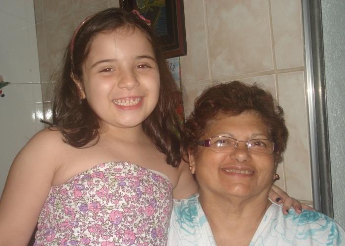 """Camila Arolde Silva, de 8 anos, posa sorridente ao lado da vovó Maria Santa Soares Arolde. A mãe da garota costuma dizer: """"Não seríamos nada sem a vovó!""""."""