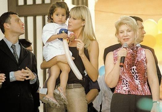 Ao lado da então prefeita de São Paulo, Marta Suplicy, Ana Hickmann segura criança em campanha beneficente de Natal (ago.2003)