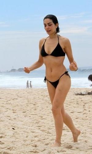 30.out.2011 - A bela Letícia Sabatella usa um bíquini preto que valoriza sua boa forma, enquanto curte a praia do Leblon, no Rio