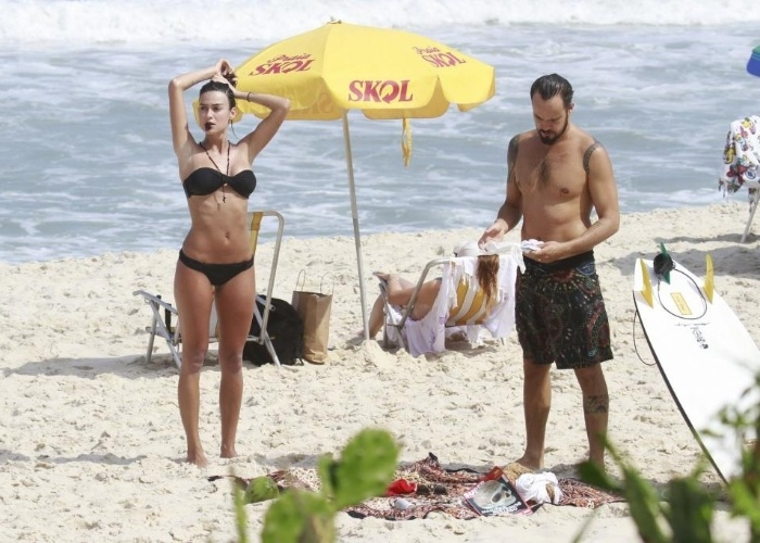 8.mar.2013 - O casal Paulinho Vilhena e Thaila Ayala curte dia ensolarado na Prainha, no Rio de Janeiro. O ator aproveitou para surfar enquanto Thaila renovava o bronzeado nas areias do local