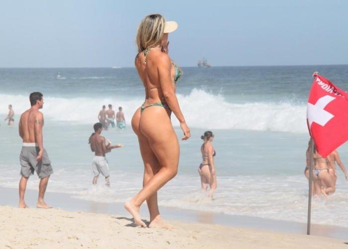 10.mar.2013 - Andréa de Andrade, madrinha de bateria da escola de samba Império de Casa Verde, exibe corpo musculoso na praia da Barra da Tijuca, no Rio de Janeiro. A loira foi acompanhada do filho, Rinaldo