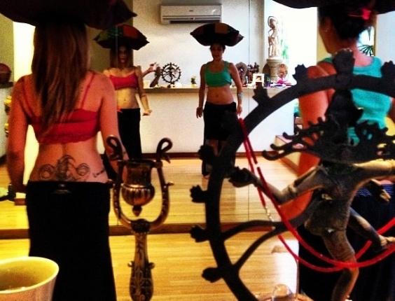 30.mar.2013 - Cleo Pires está empenhada nas aulas de dança turca para a novela 'Salve Jorge'. A atriz publicou uma foto em seu Instagram, neste sábado, em que aparece equilibrando uma almofada na cabeça, ao lado da professora Patrícia Passos.