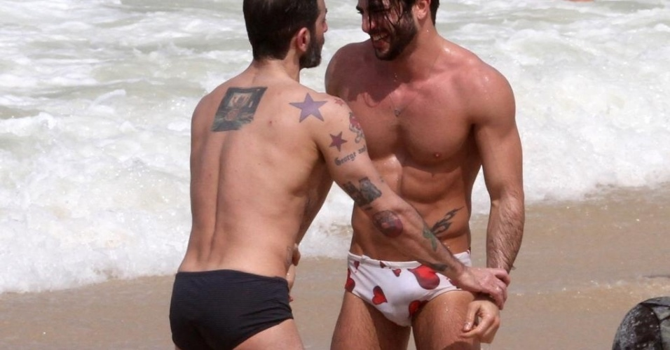 7.abr.2013 - O estilista americano Marc Jacobs (de sunga preta) e o namorado, Harry Louis, trocam beijos e carinhos na praia de Ipanema, no Rio de Janeiro