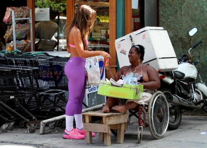 12.abr.2013 - Nicole Bahls ajuda cadeirante após fazer compras em um mercadinho no Rio de Janeiro. A ex-panicat aparece em público após o suposto abuso cometido contra ela pelo diretor teatral Gerald Thomas, que tentou pôr a mão por baixo de seu vestido em um evento no último dia 10 de abril