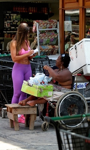 12.abr.2013 - Nicole Bahls d autgrafo a cadeirante aps fazer compras em um mercadinho no Rio de Janeiro. A ex-panicat aparece em pblico aps o suposto abuso cometido contra ela pelo diretor teatral Gerald Thomas, que tentou pr a mo por baixo de seu vestido em um evento no ltimo dia 10 de abril