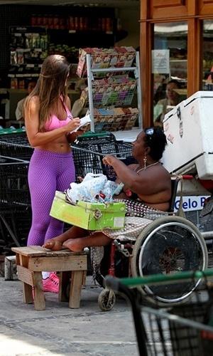 12.abr.2013 - Nicole Bahls dá autógrafo a cadeirante após fazer compras em um mercadinho no Rio de Janeiro. A ex-panicat aparece em público após o suposto abuso cometido contra ela pelo diretor teatral Gerald Thomas, que tentou pôr a mão por baixo de seu vestido em um evento no último dia 10 de abril