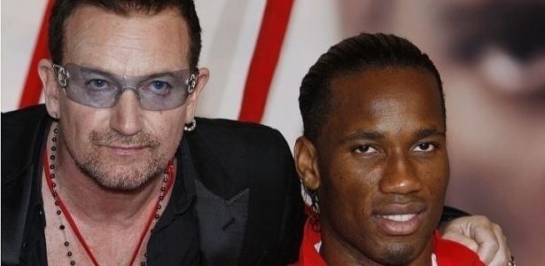Jul.2010 - Bono Vox e o jogador de futebol Drogba posam juntos em evento para o combate à Aids