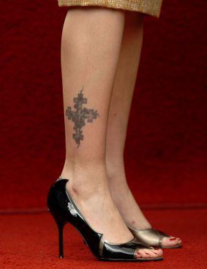 As pernas de Drew Barrymore têm uma cruz que simboliza os quatro evangelistas