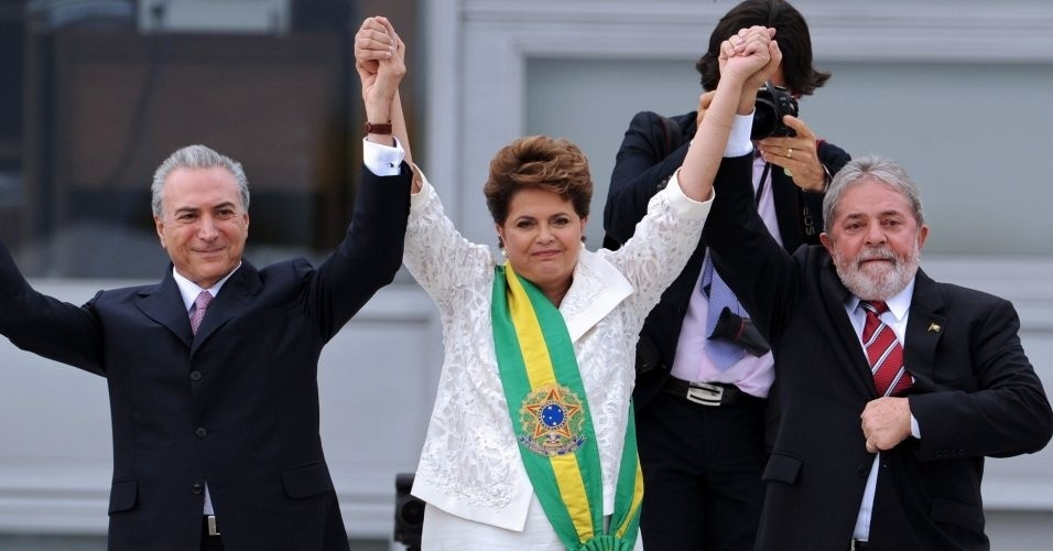 1.jan.2011 - Com a faixa presidencial, Dilma segura nas mãos de seu vice, Michel Temer, e do ex-presidente Lula, durante cerimônia de posse em Brasília.