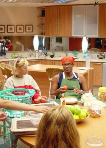 Participantes do BBB1 reunidos na mesa da cozinha. Primeira moradia dos BBBs tinha visual simples em tons de madeira clara