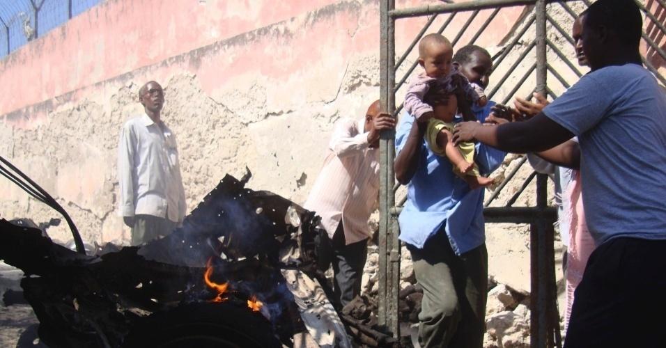 Homem carrega criança próximo a destroços de carro que explodiu no centro de Mogadício, na Somália, deixando duas pessoas feridas