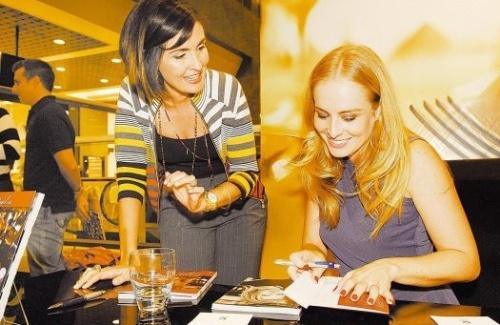 """A apresentadora autografa o livro """"Cozinha das Estrelas"""", com receitas de famosos, para a jornalista Fátima Bernardes (8/5/08)."""