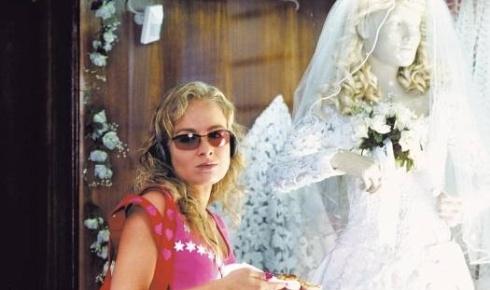 Angélica é fotografada com um vestido de noiva ao fundo na época em que protagonizou o filme 'Um Show de Verão', de Moacyr Góes, ao lado de Luciano Huck, seu atual marido (jan.2004).