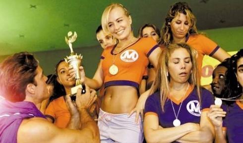 Exibindo um corpo 'sequinho', Angélica ganha troféu no 'Papo Irado', protagonizado pela adolescente Tati (Heloísa Périssé, de braços cruzados), do 'Fantástico' (jul.2003).