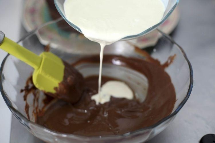Agora, faça a cobertura de ganache. Derreta os chocolates (no micro-ondas ou em banho-maria) e acrescente o creme de leite