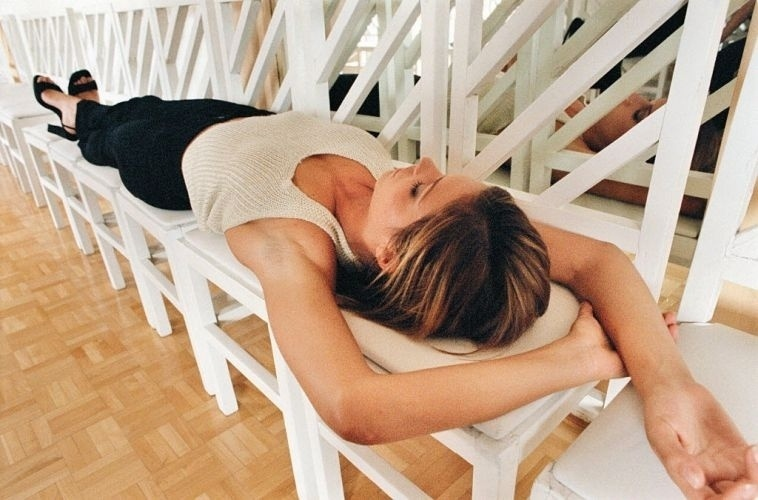 A modelo Fernanda Lima descansa sobre cadeiras antes do desfile de Marie Toscano (11/2/98)