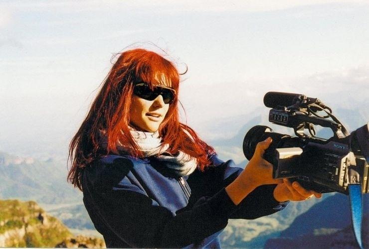 """Com uma câmera portátil, a apresentadora de TV Fernanda Lima se prepara para praticar voo-livre em Urubici, Santa Catarina; cena do programa """"Mochilão"""", da MTV (20/11/03)"""