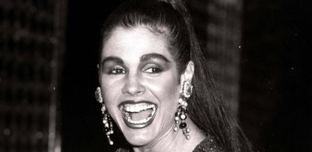 Com os cabelos escuros e maquiagem carregada, Monique sorri para fotógrafo em imagem de 1986