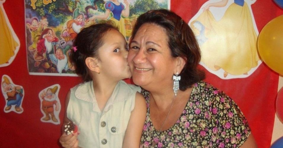 Sofia Ayda mima a avó Santa Oliveira, em Ibirité (MG).
