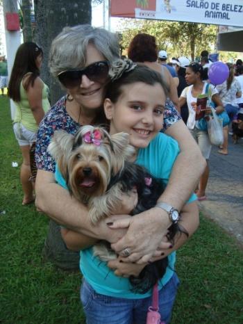 afaela Simões abraça a neta Gabriela e a cadelinha da família em um evento realizado na cidade de Santos (SP).