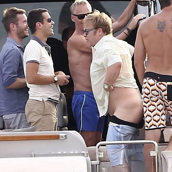 Elton John passeava tranquilamente de iate em Saint Tropez com o marido, David Furnish, e amigos quando se viu bisbilhotado por paparazzi e curiosos de plantão (13/8/12). Aos 65 anos, o cantor não teve dúvida sobre o que fazer: virou-se de costas e tirou a bermuda
