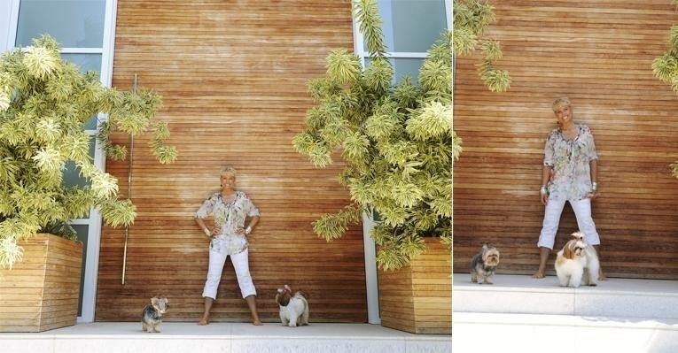 """Xuxa Meneghel posa em frente à porta principal de sua casa, no Rio de Janeiro. A apresentadora mostrou ambientes de sua casa ecologicamente correta à revista """"Caras"""". É a primeira vez que a apresentadora mostra o lar para um veículo de comunicação (novembro de 2011)"""