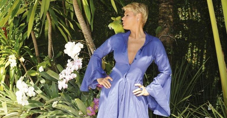 """Xuxa Meneghel faz carinho no papagaio Lolo. A loira disse, em entrevista à revista """"Caras"""", que seu coração está tranquilo, mas que pensou que beijaria muito mais neste ano, """"mas não aconteceu"""" (novembro de 2011)"""