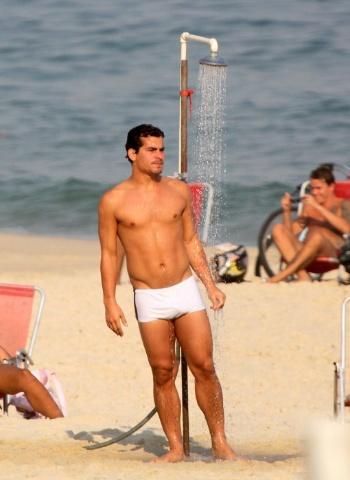 Thiago Martins toma ducha na praia da Barra da Tijuca, no Rio de Janeiro. O ator aproveitou o dia de seu aniversário de 24 anos ao lado da namorada, a atriz Paloma Bernardi e amigos (19/9/12)