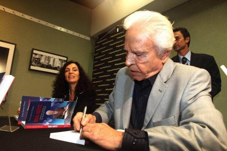 """Cid Moreira no lançamento do livro """"Boa Noite"""". A obra é uma biografia do apresentador, de autoria de sua mulher, a jornalista Fátima Moreira (ao fundo) (23/3/10)"""