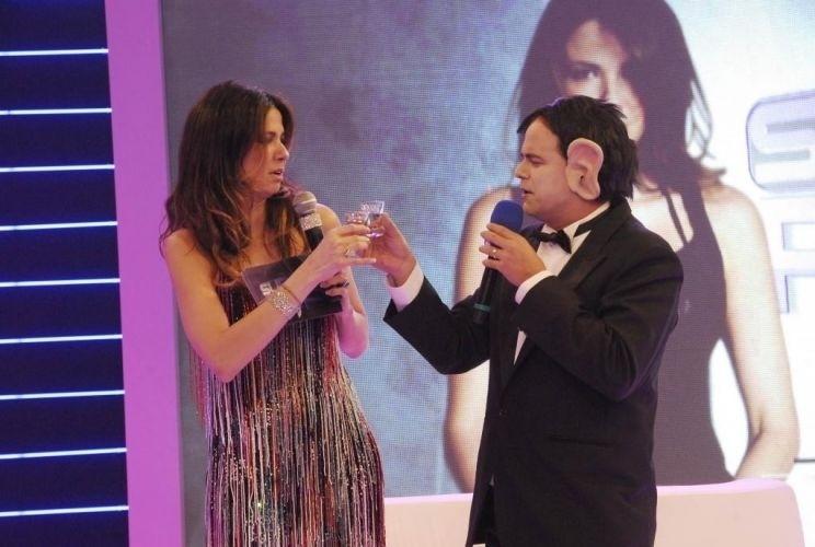 """Luciana Gimenez brinda com Amaury Dumbo (personagem do Carioca, do """"Pânico"""") na festa de lançamento do novo cenário do programa """"Superpop"""", em São Paulo (26/1/10)"""