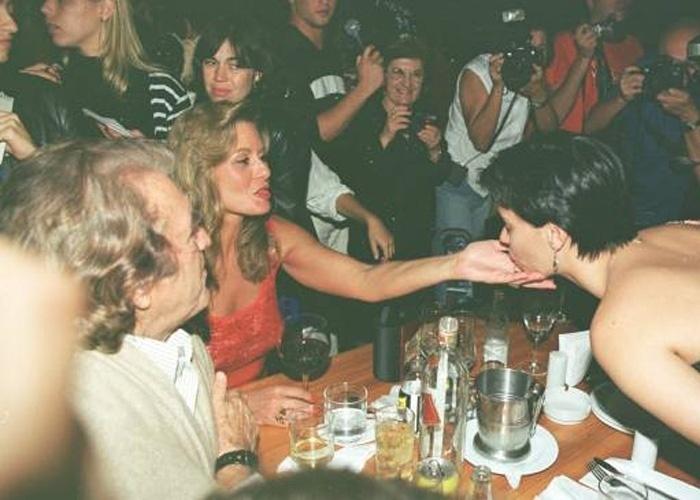 """Carolina Dieckmann, de cabelos curtinhos e escuros, beija a mão de Vera Fischer durante reunião para assistir ao primeiro capítulo da novela """"O Clone"""" (Outubro/2001)"""