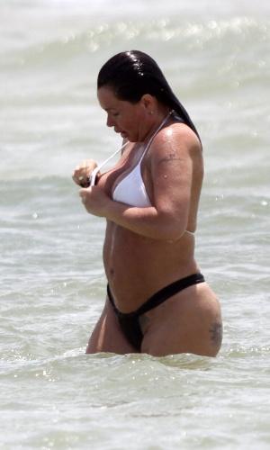 1.dez.2012 - A ex-modelo Cristina Mortágua foi à praia da Barra da Tijuca, na Zona Oeste do Rio de Janeiro. A ex de Edmundo não quis ficar com marquinhas e se bronzeou sem a parte de cima do biquíni, mas acabou deixando um pouco do seio à mostra ao dar um mergulho