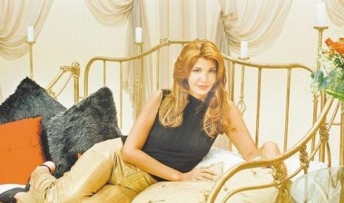"""De cabelos loiros, Roberta Close mostra cenário do programa """"De Noite na Cama"""", do Shoptime, em 2000"""