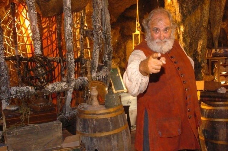 """2004 - Um papel de grande destaque na carreira de Elias Gleizer foi como Bartô em """"Como Uma Onda"""". Nesta obra, o ator fazia um navegador europeu que vivia recluso em uma caverna rodeada de antiguidades e pequenos tesouros"""