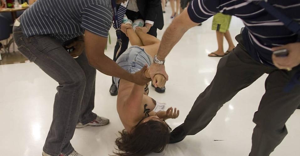"""8.Jan.2013 - Seguranças arrastam integrante do Femen que invadiu o shopping Santana Plaza para protestar contra a casa de vidro do """"Big Brother Brasil 13"""""""