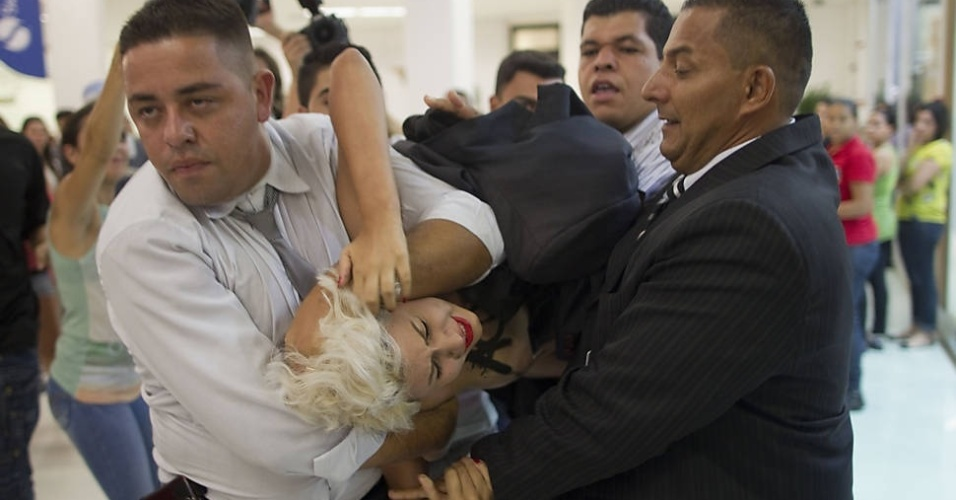 """8.Jan.2013 - Seguranças entram em confronto com integrantes do Femen que estavam protestando contra a casa de vidro do """"Big Brother Brasil 13"""""""
