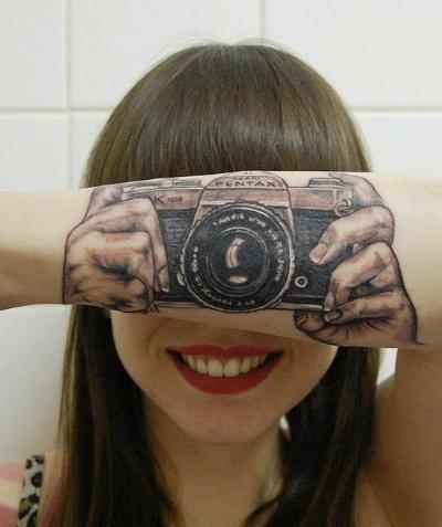 18.jan.2013 - A fotógrafa holandesa Lotte van der Acker, de 24 anos, tem em seu braço uma tatuagem que é uma ilusão de ótica. A imagem, que simula que ela está usando uma máquina fotográfica, foi feita pela tatuadora e mãe da jovem, Helma van der Weide. O desenho é a reprodução do modelo Pentax Asahi 35mm dos anos 70.