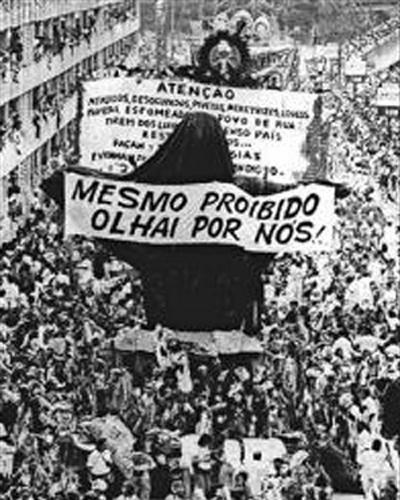 """O carnavalesco Joãozinho Trinta (1933-2011) """"chocou a sociedade"""" ao colocar um Cristo Redentor vestido de mendigo em um dos carros alegóricos da Beija-Flor. Porém, uma decisão judicial proibiu que a escola exibisse o ornamento no desfile. Joãosinho Trinta não deixou por menos: cobriu a alegoria com um plástico preto e a exibiu no desfile com a frase """"Mesmo proibido, olhai por vós"""""""