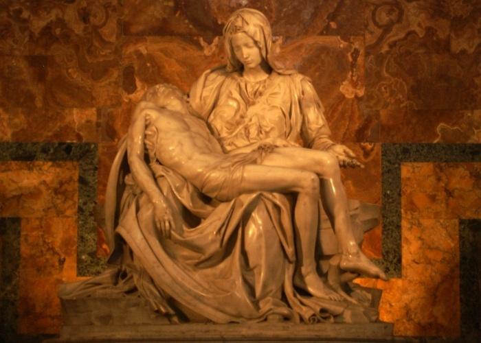 """O maior e mais popular tesouro artístico exposto na basílica de São Pedro é a """"Pietà"""", estátua esculpida em mármore de Carrara por Michelangelo e finalizada em 1499. O mestre renascentista terminou aos 25 anos a escultura, que representa a Virgem Maria aconchegando no colo Jesus morto."""