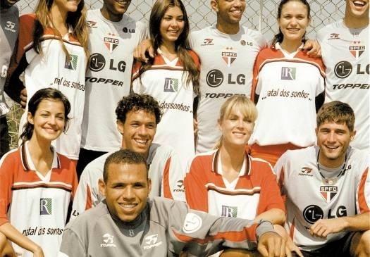 Ana e outras modelos posam ao lado de jogadores do São Paulo durante treino da equipe (ago.2003)
