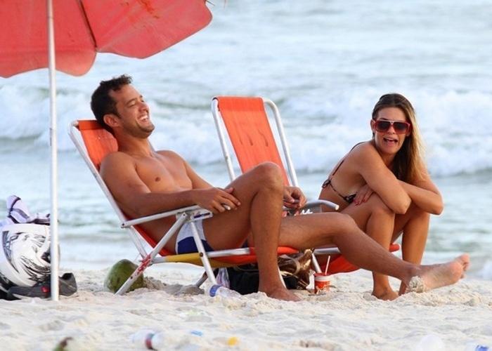 4.mar.2013 - Acompanhada de um amigo, a apresentadora Lívia Lemos curte o calor carioca na praia da Barra da Tijuca (RJ)