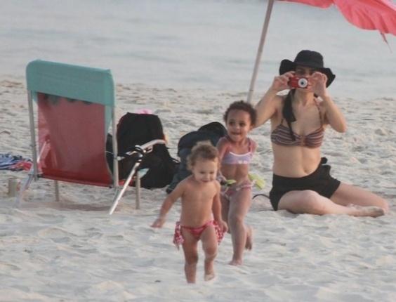 9.fev.2012 - Com um chapéu e uma máquina fotográfica em mãos, Letícia Sabatella brinca com crianças em praia do Rio. A atriz esteve na Barra da Tijuca, na zona oeste da cidade