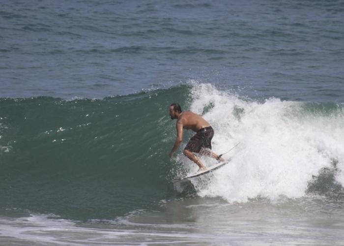 8.mar.2013 - Paulinho Vilhena pega onda na Prainha, no Rio de Janeiro, enquanto Thaila Ayala tomava sol no local