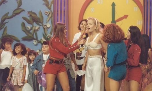 """Com apenas 13 anos, Juliana Silveira (segurando o microfone) começou sua carreira na televisão. Na época, ela atuava como assistente de palco da apresentadora Angélica. O programa era """"Casa da Angélica"""", que foi exibido pelo SBT (1993)"""