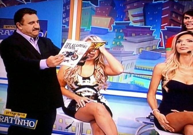 """9.abr.2013 - A capa da revista """"Sexy"""" de abril, Ísis Gomes, participou do """"Programa do Ratinho"""", no SBT. A beldade usou um microvestido e brincou com o apresentador e sua trupe de humoristas, além de exibir suas curvas fartas. Em seu Twitter, a gata comentou como foi participar do programa: """"Amei minha participação no Ratinho, ele é um amor, e acho que saí do programa apaixonada pelo Marquito"""", brincou. Na foto, Ratinho folheia a revista com o ensaio nu de Ísis"""